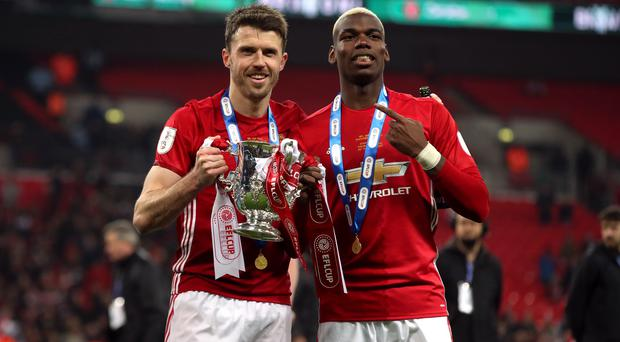 Michael Carrick, left, is confident Paul Pogba will not leave Old Trafford