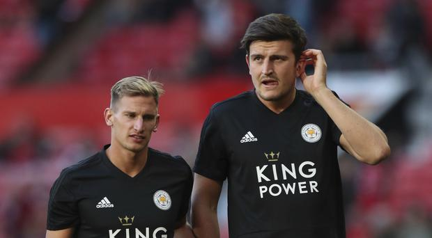 Leicester City's Harry Maguire, right, takes part in the warm up prior to the start of the English Premier League soccer match between Manchester United and Leicester City at Old Trafford, in Manchester, England, Friday, August, 10, 2018. (AP Photo/Jon Super)