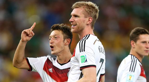 Joachim Low was at Arsenal's training ground to visit Per Mertesacker, centre, and not Mesut Ozil, left (Mike Egerton/PA)