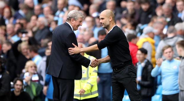 Pep Guardiola, right, does not intend to manage for as long as Roy Hodgson (Nick Potts/PA)