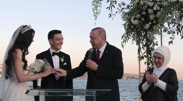Turkey's President Recep Tayyip Erdogan speaks to Turkish-German soccer player Mesut Ozil and his wife Amine Gulse during a wedding ceremony over the Bosporus in Istanbul, Friday, June 7, 2019. Erdogan's wife Emine Erdogan is at right. (Presidential Press Service via AP, Pool)