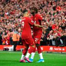 Divock Origi and Roberto Firmino of Liverpool celebrate after Grant Hanley of Norwich City scores an own goal
