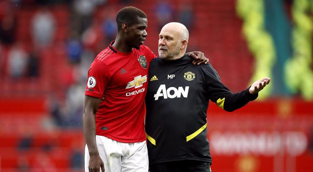 Paul Pogba and United's assistant manager Mike Phelan, right, enjoy Sunday's opening-day win (Martin Rickett/PA)