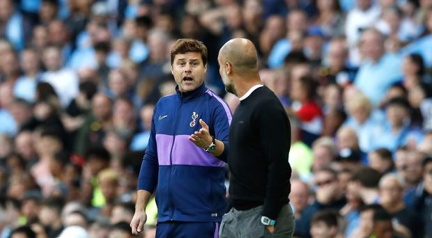 Manchester City manager Pep Guardiola (right) in conversation with Tottenham counterpart Mauricio Pochettino (Martin Rickett/PA)