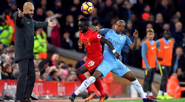 Pep Guardiola, left, has accused Liverpool's Sadio Mane, centre, of diving (Dave Howarth/PA)