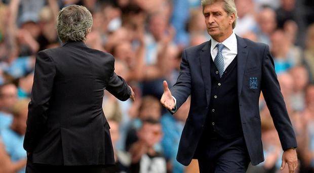 Shake it on: Jose Mourinho and Manuel Pellegrini approach each other after the clash at the Etihad