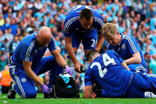 Running repairs: An injured Gary Cahill receives attention from Chelsea's medical team as John Terry looks on