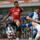 Stuck in: Marcus Rashford battles for the ball at Ewood Park