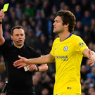 Lucky escape: Marcos Alonso is booked by Suart Attwell