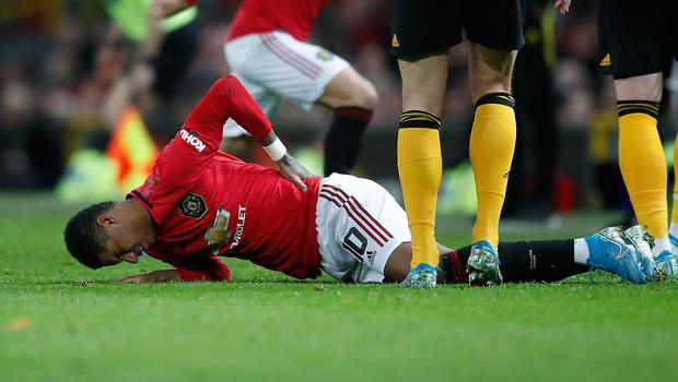 Marcus Rashford holds his back after suffering the injury against Wolves (Martin Rickett/PA)