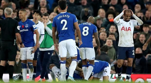 Cenk Tosun (second right, 14) tried his best to comfort injured team-mate Andre Gomes (bottom, centre) (Nick Potts/PA)