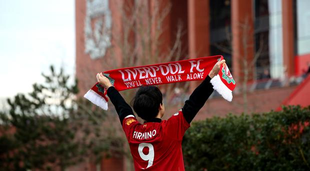 A Liverpool supporter wearing a Firmino top holds up a scarf outside Anfield (Nick Potts/PA)