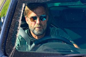 At wheel: manager Jurgen Klopp leaves Liverpool's training ground at Melwood yesterday