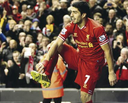Right on: Luis Suarez points to his boot after scoring at Anfield