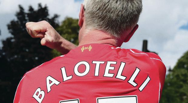Getting shirty: A Liverpool fan models his Mario Balotelli jersey