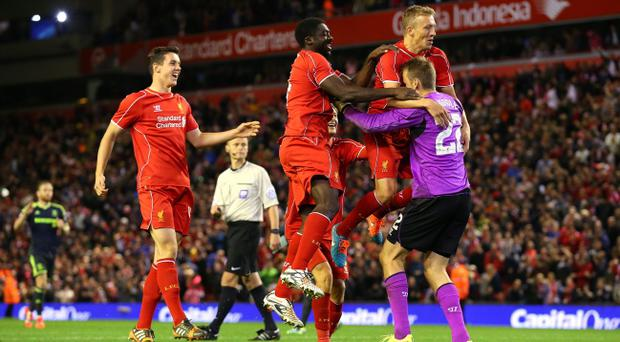 Lucas, Kolo Toure and Simon Mignolet of Liverpool celebrate after winning the match on penalties after a miss from Albert Adomah of Middlesbrough during the Capital One Cup Third Round match between Liverpool and Middlesbrough at Anfield