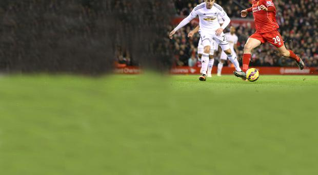 Goal-den touch: Adam Lallana shoots and scores Liverpool's third goal last night against Swansea