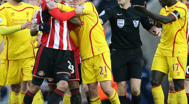 Fighting for their teams: Liverpool's Lucas Leiva (21) and Black Cats' Santiago Vergini scuffle over claims of time-wasting