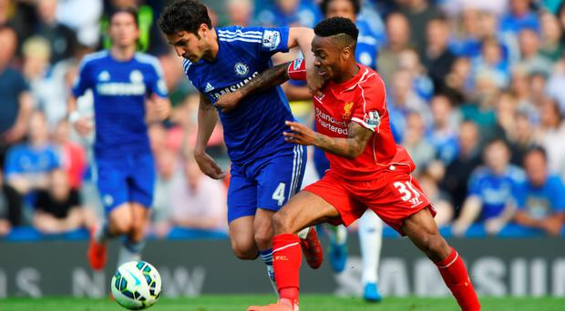 Crying foul: Raheem Sterling battles with Cesc Fabregas after the Chelsea player's earlier foul on the Liverpool man