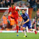 Close quarters: Liverpool's Roberto Firmino holds off Cesc Fabregas during the Premier League clash at Anfield