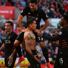 Victory march: Roberto Firmino is mobbed after firing in Liverpool's winner