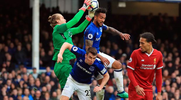 Heads up: Liverpool keeper Loris Karius takes the ball off the head of Everton striker Theo Walcott