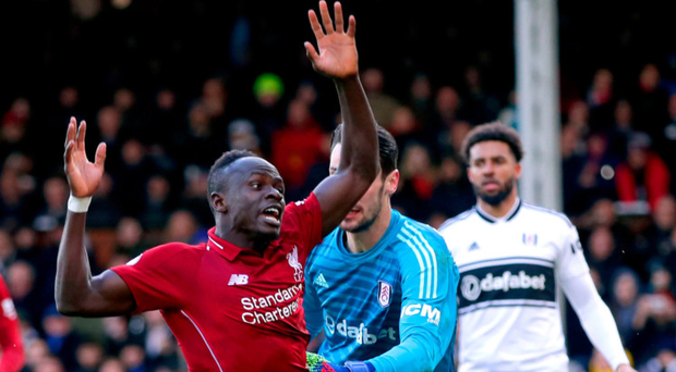 Pulling power: Liverpool's Sadio Mane falls following a penalty box tangle with Fulham goalkeeper Sergio Rico