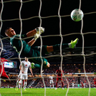 Net loss: MK Dons goalkeeper Stuart Moore can't react in time to keep James Milner's strike out