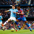 Close watch: John Stones tracks Wilfried Zaha during the 2-2 draw at the Etihad