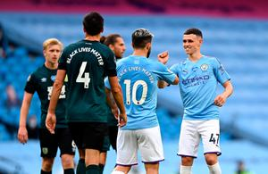 Great start: Phil Foden celebrates with Sergio Aguero after opening the scoring in City's win over Burnley
