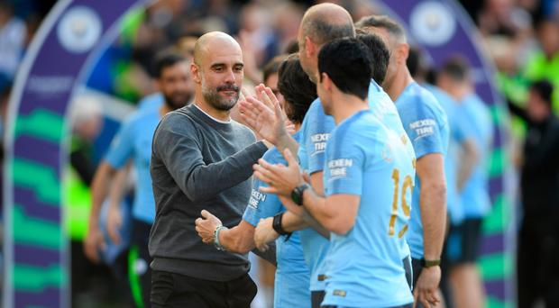 High fives: Pep Guardiola congratulates his staff
