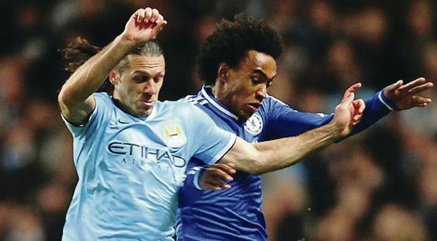 MANCHESTER, ENGLAND - FEBRUARY 03: Martin Demichelis of Manchester City and Willian of Chelsea fight for the ball during the Barclays Premier League match between Manchester City and Chelsea at Etihad Stadium on February 3, 2014 in Manchester, England. (Photo by Laurence Griffiths/Getty Images)