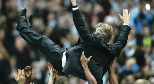 Top boss: Manuel Pellegrini is thrown up into the air and caught by his Manchester City players yesterday afternoon