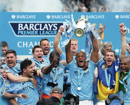 Champions: Man City captain Vincent Kompany lifts the Premier League trophy with his team-amtes by his side after their 2-0 win over West Ham yesterday