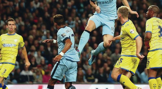 Net bonus: Edin Dzeko scores City's fifth goal against Sheffield Wednesday last night