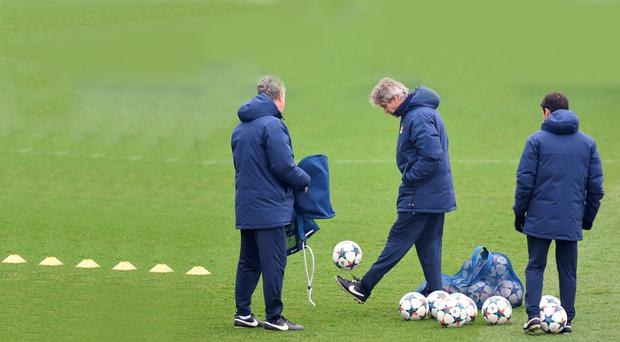 Juggling act: Manuel Pellegrini shows his ball skills to coach Brian Kidd during training ahead of Manchester City's clash with Barcelona