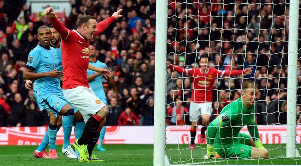 It's there: Wayne Rooney celebrates as Manchester United team-mate Ashley Young's effort enters the Man City net
