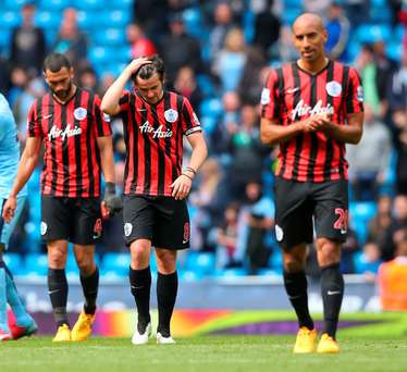 Down and out: Defeated Queens Park Rangers players trudge off after their relegation was confirmed at Manchester City