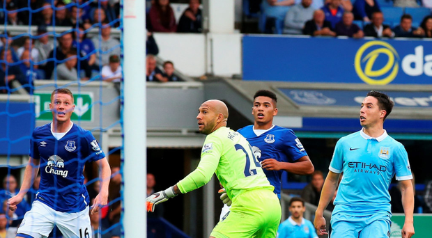 Chipping in: Samir Nasri guides the ball over Tim Howard's head to score Manchester City's second goal