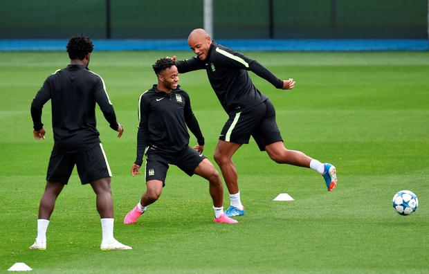 Going to the flicks: Vincent Kompany tries a trick to beat Raheem Sterling in training