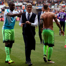 Suits you: Yaya Toure encourages Manuel Pellegrini to give his Manchester City suit jacket to a fan in the crowd at the Etihad Stadium, with the Chilean boss duly obliging after seeing his side draw 1-1 with Swansea in his final game in charge