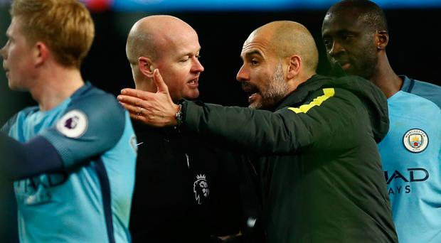Making his point: Pep Guardiola remonstrates with referee Lee Mason, who sent off Fernandinho during Manchester City's 2-1 win over Burnley