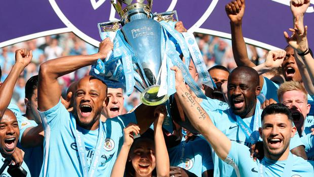 Huge lift: Manchester City captain Vincent Kompany and Sergio Aguero hoist aloft the Premier League trophy after the scoreless draw with Huddersfield yesterday to get the party started at the Etihad Stadium