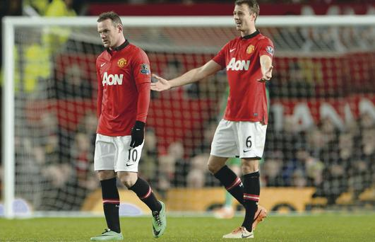 MANCHESTER, ENGLAND - JANUARY 01: Wayne Rooney of Manchester United and his team-mate Jonny Evans react after conceding a second goal during the Barclays Premier League match between Manchester United and Tottenham Hotspur at Old Trafford on January 1, 2014 in Manchester, England. (Photo by Michael Regan/Getty Images)
