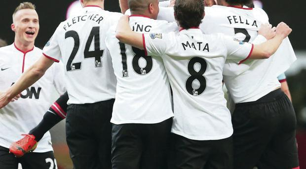 Touch of genius: Wayne Rooney is mobbed in celebration by his Manchester United team-mates after his wonder strike