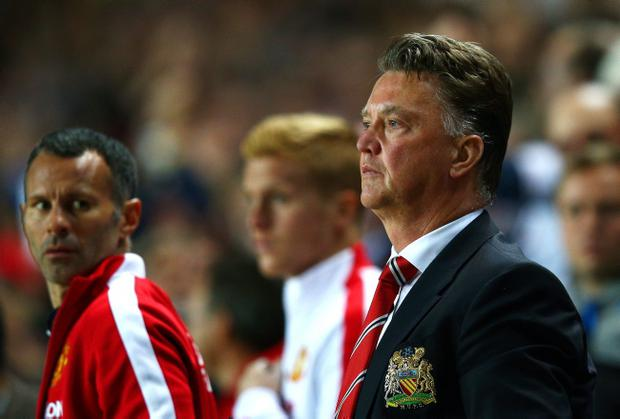 Manchester United manager Louis van Gaal looks dejected with assistant Ryan Giggs after the 4-0 hammering to MK Dons in the Capital One Cup last night