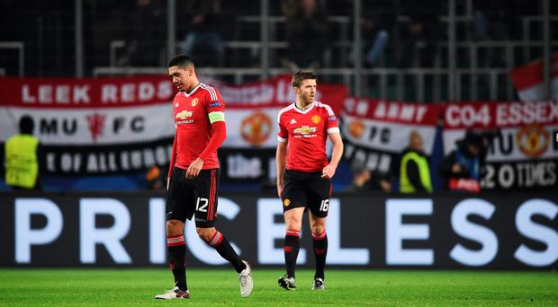 Out: Chris Smalling and Michael Carrick of Manchester look dejected during the UEFA Champions League match between VfL Wolfsburg and Manchester United