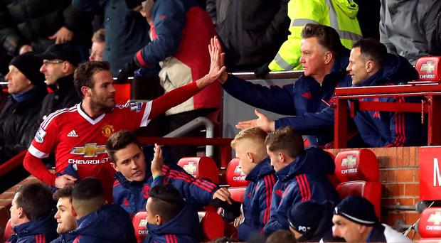Seal of approval: Manchester United manager Louis van Gaal high fives Juan Mata after his substitution