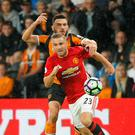 On the ball: Manchester United's Luke Shaw is challenged by Hull's Robert Snodgrass