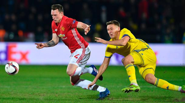 Eyes on the prize: Manchester United ace Phil Jones gets away from Aleksandr Bukharov of Rostov during the 1-1 draw in Russia
